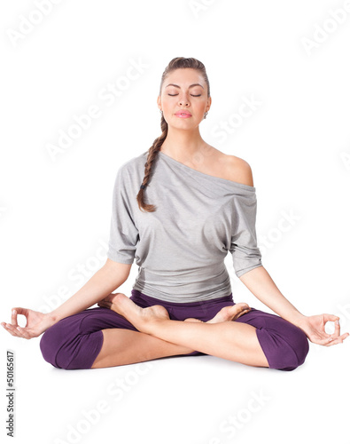 Young woman doing yoga exercise Padmasana (Lotus Pose).