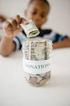 Black Boy Putting Money Into Donations Jar