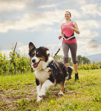 Caucasian Woman Running With Dog