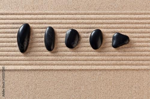Acrylic Prints Stones in Sand Five black pebbles on raked sand