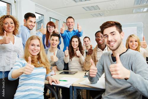 Fotografia  Studenten halten Daumen hoch in der Uni