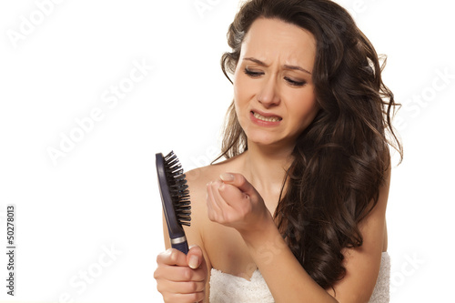 Fotografia  girl is very nervous about the loss of hair on white background