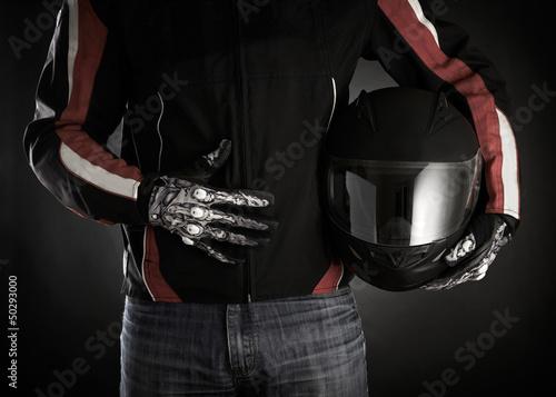 Fotografia Motorcyclist with helmet in his hands. Dark background