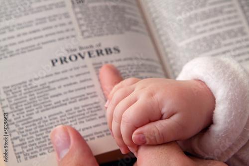Fotografie, Obraz  Baby Holding Dad's Finger on Bible