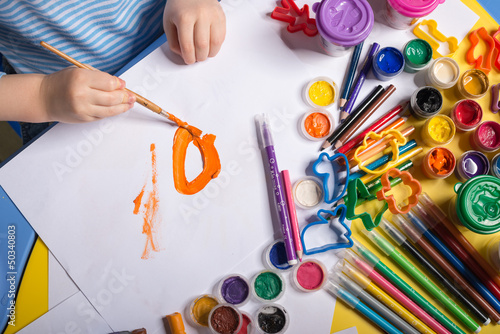 Hands of painting little boy