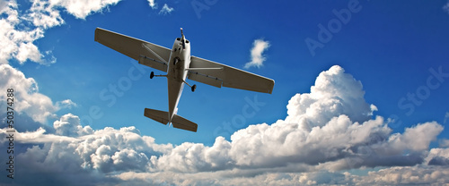 Small light aircraft on training flight Fototapeta