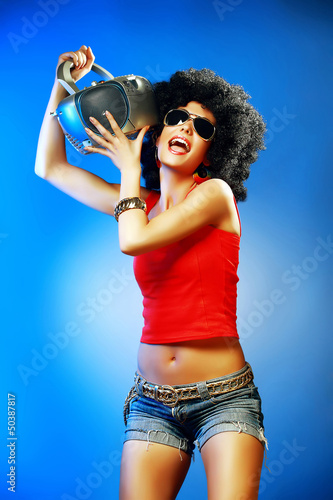 Fotografia  Happy tanned woman enjoying music holding tape recorder.