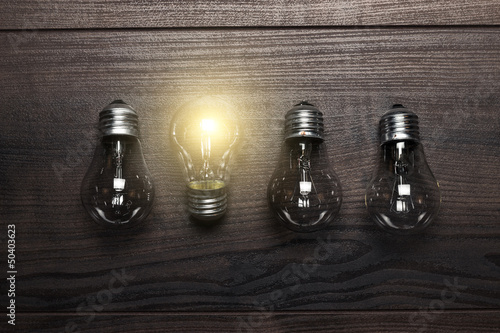 Fotografía  glowing bulb uniqueness concept on wooden background