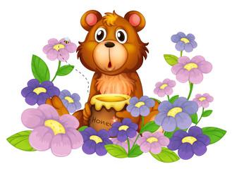 Medvjed koji drži med u cvjetnjaku