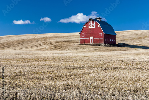 Fotografie, Obraz  Red barn blue sky and wheat stuble field