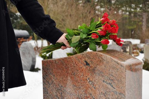 Photo sur Toile Cimetiere Junge Frau legt Blumen nieder