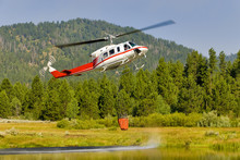 Small Helicopter Dips Water Out Of A Mountaiin Pond