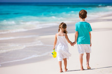 Two Kids Walking Along A Beach...