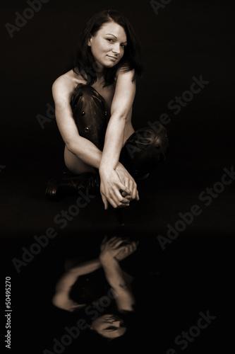 Kobieta naga w długich butach z lustrzanym odbiciem.