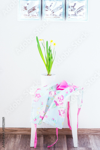 daffodil in a pot on a white stool against a white wall