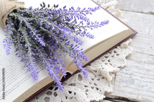 Valokuva  Bunch of lavender laying upon open book on vintage doily