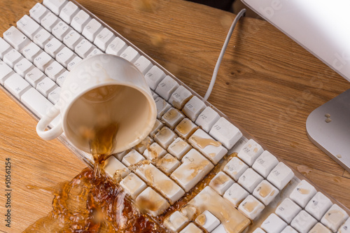 Fotografering  Cup of tea spilling over a keyboard