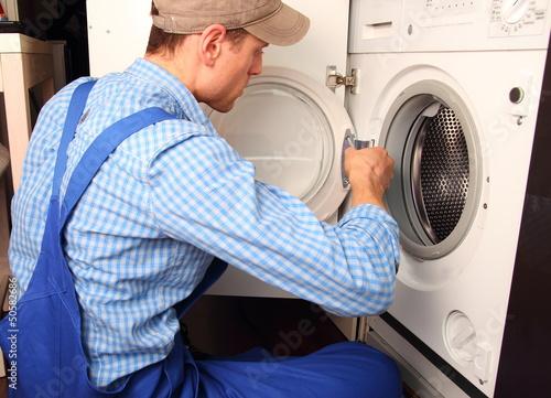 Fotografia, Obraz  Handwerker repariert Waschmaschine Seitenansicht