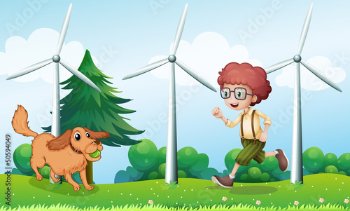 Tuinposter Honden A boy playing with his dog near the windmill