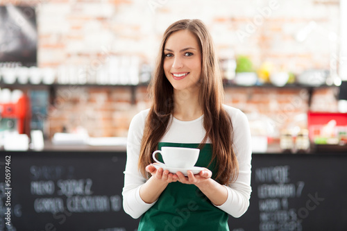 Waitress holding cup of coffee in cafe