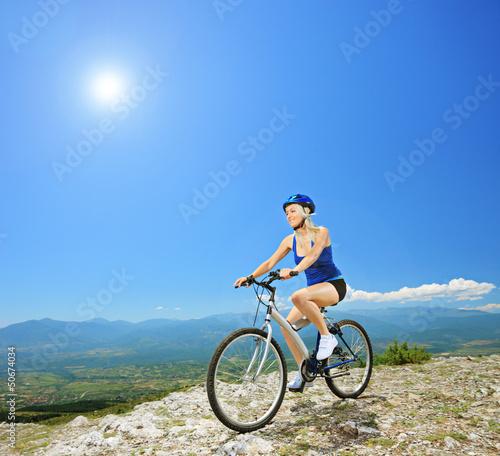 Fototapeta View of a female biker on a bike posing outside obraz na płótnie