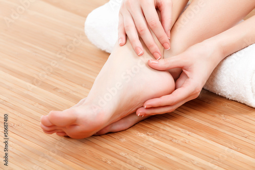 Poster Pedicure female feet and hands with a white rolled towel