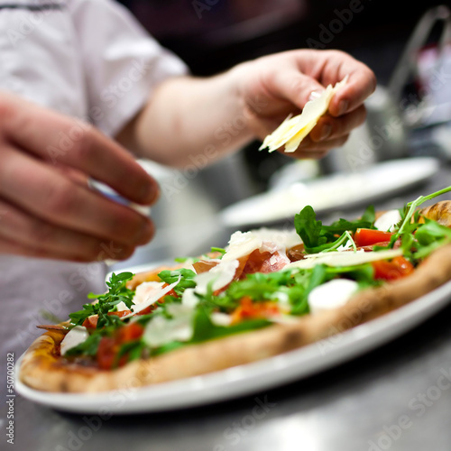 Closeup hand of chef baker in white uniform making pizza at kitc Wallpaper Mural