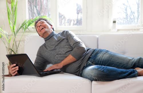 Fotografie, Obraz  Mann mit Laptop Zuhause auf dem Sofa liegend