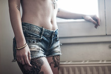 Close Up Of Beautiful Girl With Tattoo Wearing Jeans Short Paint