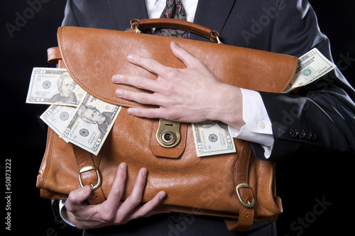 Obraz na plátně Closeup of man holding briefcase with money spilling out