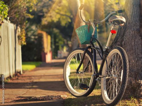 In de dag Fiets Retro bicycle on sunny street. Focus on rear wheel.