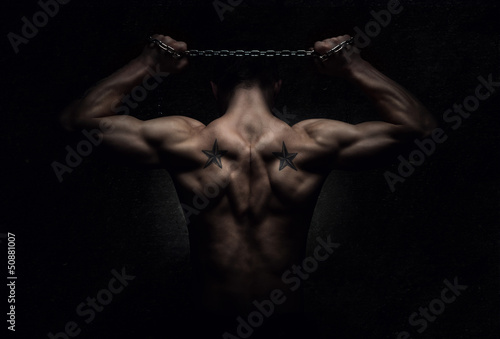 Muscular sports man stretching out over dark background Wallpaper Mural