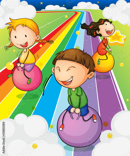 In de dag Regenboog Three kids playing with the bouncing balls at the colorful road