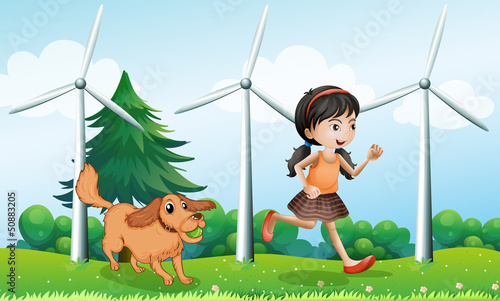 Tuinposter Honden A girl playing with her dog near the windmills
