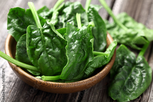 Vászonkép Spinach leaves in a wooden plate