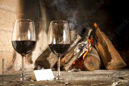 Spoed Foto op Canvas Wijngaard Copas de vino tinto con chimenea y fuego de fondo.