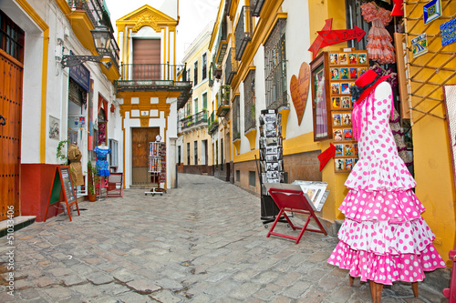 Shopping street with typical flamenco dress in Seville, Spain. Fotobehang