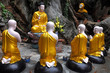 Gold sitting Buddha surrounded by monk students, Vietnam