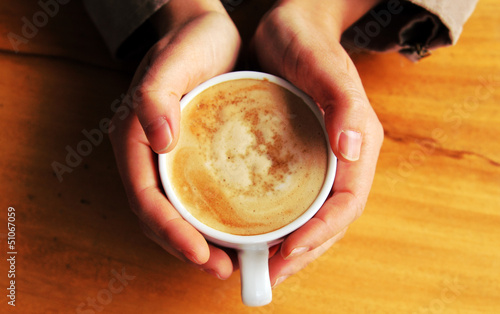 woman holding hot cup of coffee with brown sugar