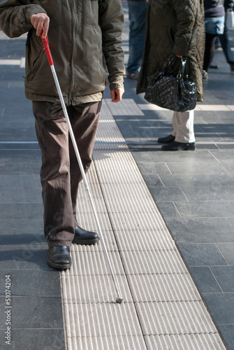 Blind person with white cane in public space Wallpaper Mural