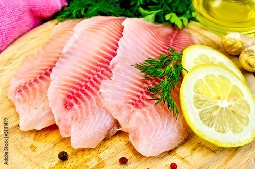 Leinwand Poster Fillets tilapia with oil and lemon