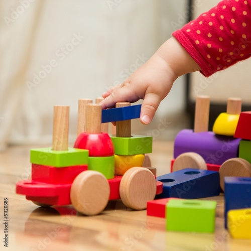 Fotografie, Obraz  Baby's hand playing with wooden toys
