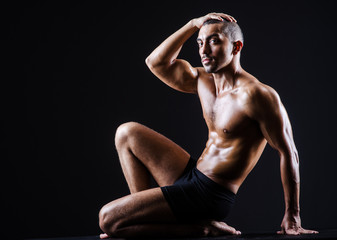Fototapeta Muscular man in dark studio