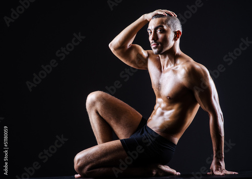 Muscular man in dark studio - 51180059