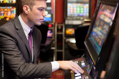 Fotografija  Men gambling in the casino on slot machines