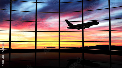 Deurstickers Luchthaven Airport window with airplane flying at sunset