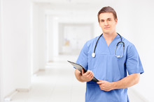 A Male Medical Doctor In A Uniform Holding A Clipboard And Posin