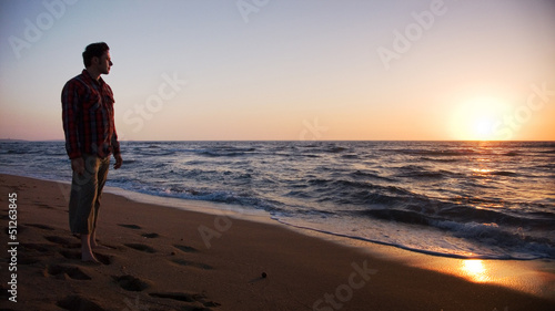 Man standing on the beach and looking into sunset Canvas Print