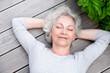 canvas print picture - grauhaarige Frau entspannt auf der Terrasse