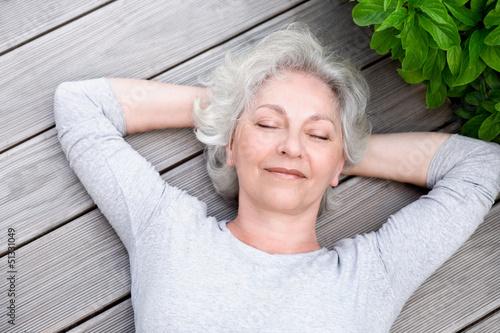 Obraz grauhaarige Frau entspannt auf der Terrasse - fototapety do salonu